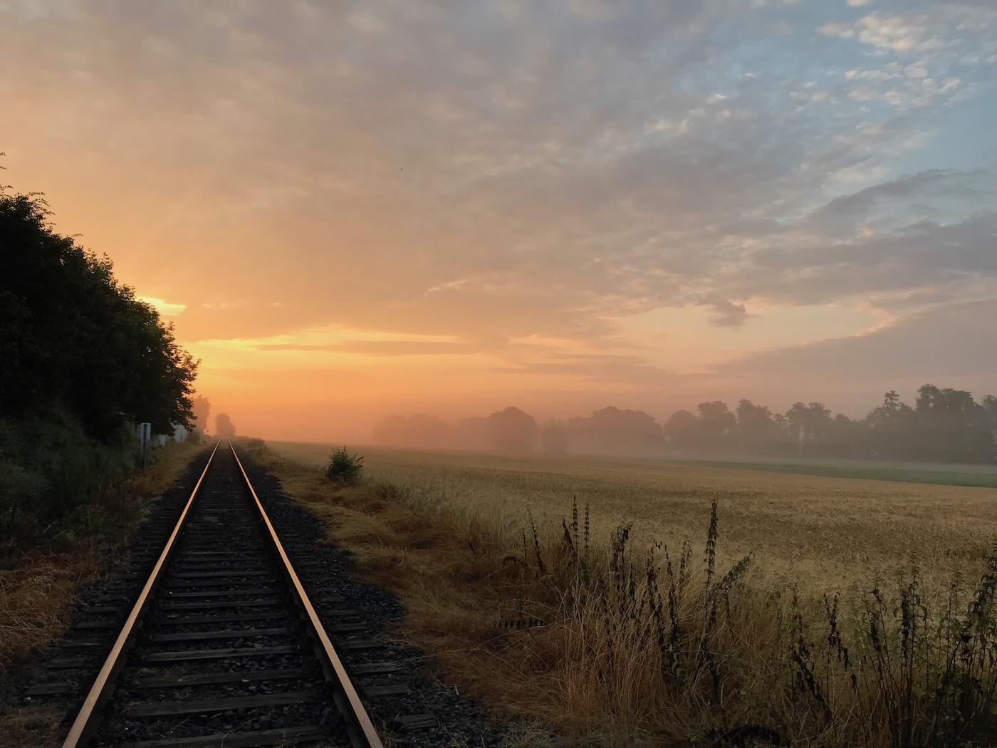 Sonnenaufgang an Bahnschiene im Feld
